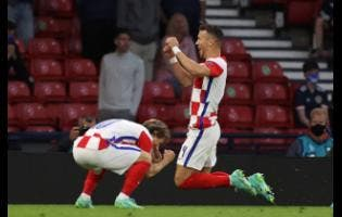 Croatia's Ivan Perisic (right) celebrates with Luka Modric after scoring his side's third goal during the Euro 2020 Group D match between Croatia and Scotland at the Hampden Park stadium in Glasgow yesterday. Croatia won 3-1.