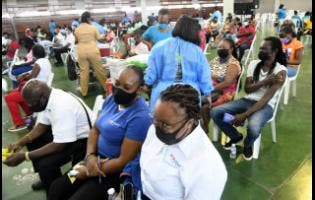 Health workers tend to persons who came out to be vaccinated at the National Arena on Tuesday as part of an islandwide vaccination blitz.