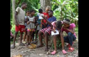 Children in Kent Village, St Catherine, catch up on some lessons while in their community last week.