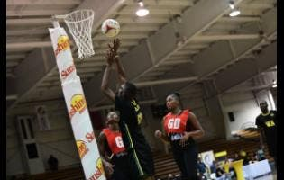 Trinidad and Tobago's Anilcia Baptiste (left) and Shaquanda Greene-Noel look on as Jamaica's Raheem Wallace takes a shot during the Trinidad and Tobago Calypso Girls vs Jamaica men exhibition netball match at the National Indoor Sports Centre on Thursday, October 14. The Sunshine Girls will take on the Jamaica men's team in an exhibition match today at 6 p.m.
