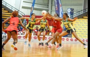 Jamaica's goal defence, Kadian Dehaney (right) and centre Adean Thomas (second left) challenge for the ball with Trinidad and Tobago's wing attack Crystal George (second right during the third and final match in the three-match Sunshine Series, at the National Indoor Sports Centre last night. Looking on are Jamaica's wing defence, Shadian Hemmings (centre) and Trinidad and Tobago's centre, Destiny Williams. Jamaica' won 73-22.
