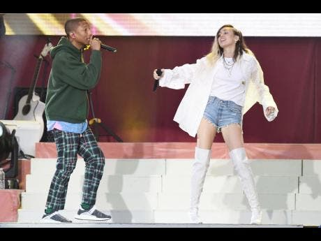 Pharrell Williams and Miley Cyrus perform at the One Love Manchester tribute concert in Manchester north western England yesterday