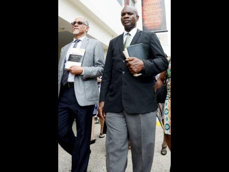 Major Richard Cooke (left) and Dr Alvin Bailey, bishop of the Holiness Christian Church, make their way to Gordon House to protest against abortion yesterday.