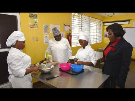 Vice-principal of the Trench Town Polytechnic College, Sandra Brown (right), looks on as year-two culinary arts students Shanika Jackson (left) and Lioney Reid (second right)  prepare to take instructions from Teisha Campbell, lecturer.