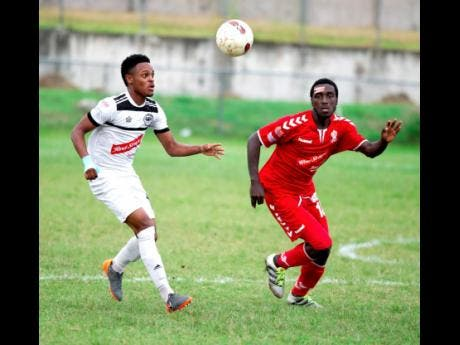 Cavalier FC's Alex Marshall (left) keeps his eyes on the ball while  UWI FC's Michael Heaven does his best to stay close to the attacker, in their Red Stripe Premier League encounter at the UWI Mona Bowl on Sunday, December 2, 2019.