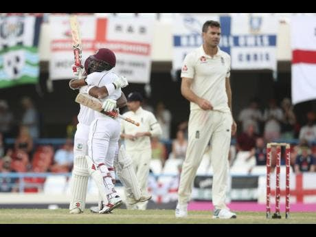 ap West Indies' John Campbell and Kraigg Brathwaite celebrate a 10-wicket victory as England's James Anderson (right) walks away disappointed during day three of the second Test match at the Sir Vivian Richards Stadium in North Sound, Antigua and Barbuda, last Saturday.
