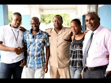 Ricardo Makyn/Chief Photo Editor Elated parents Sinclair Hutton (second left) and Suzett Whyte, thank policemen (from left) Detective constable Morvin Ellis, Superintendant Howard Chambers and Detective Inspector Phillip Dodd at the Denham Town Police Station after news broke that their baby that was stolen from the Victoria Jubilee Hospital had been found.