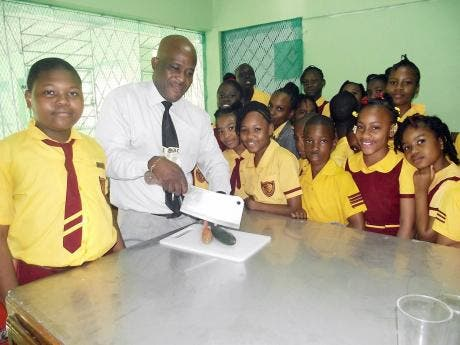 Students of Grateful Hill Primary look on as principal George Moodie prepares fresh vegetables in the new canteen.
