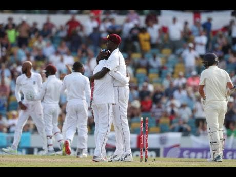 West Indies captain Jason Holder embraces a teammate at the end of day four of the first cricket Test match at the Kensington Oval in Bridgetown, Barbados, on Saturday, January 26, 2019. West Indies won by 381 runs.