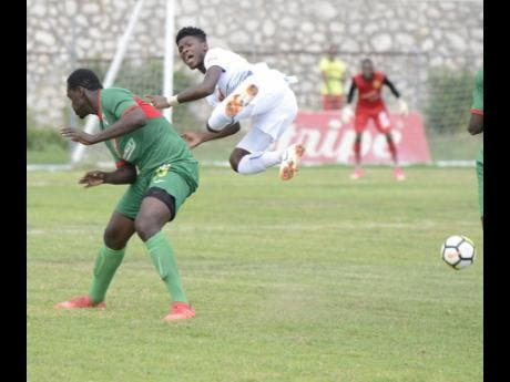 Humble Lion's Oneil 'Bigga' Thompson (left) sends Portmore United's Donnegy Fer flying from a hard tackle in their Red Stripe Premier League clash at the Spanish Town Prison Oval on Sunday, September 30, 2018.