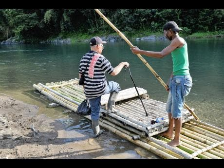 Raft captain Vincent Valentine assists a blind resident, who lives across the Rio Grande in Berrydale, Portland, to get home.