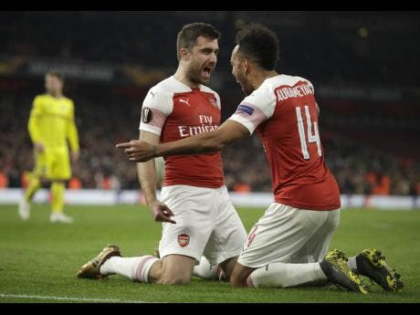 ap Arsenal's Sokratis Papastathopoulos (left) celebrates with teammate Pierre-Emerick Aubameyang after scoring his side's third goal during the Europa League round-of-32 second-leg match against BATE Borisov at the Emirates Stadium in London, England, yesterday.