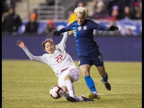 United States' Megan Rapinoe (right) tries to get around Japan's Risa Shimizu during the first half of SheBelieves Cup football match last night in Chester, Philadelphia. The game ended 2-2.