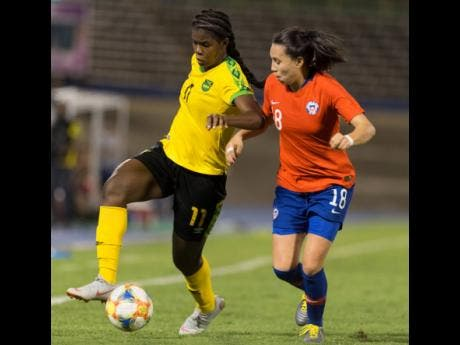 Jamaica's striker Khadija Shaw (left) dribbles the ball downfield, while being pressured by Chile's Camila Sáez during their international friendly held at the National Stadium last night. Jamaica won 1-0.