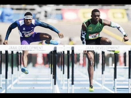 Wayne Pinnock (left) of KC  and Orlando Bennett of Calabar High in the preliminary round of the Class One boys' 110m hurdles at the 2018 ISSA/GraceKennedy Boys and Girls' Championships.