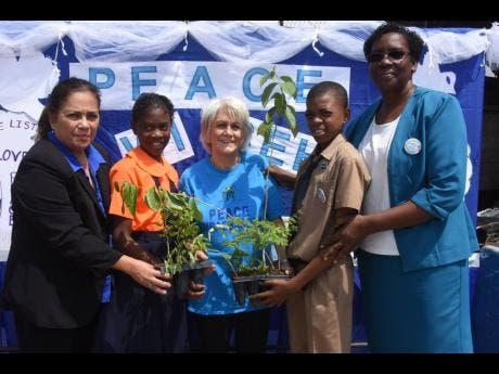 Janilee Abrikian (left), general manager of PALS, participates in Peace Day activities at Denham Town Primary School last year with (from second left) Akelia Thompson, student; Elizabeth Ward, chair of the Violence Prevention Alliance; Joshua Jeffrey, student; and Eugenie Brown, principal of the school.
