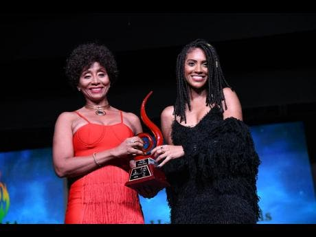 Naomi Cowan (right) receives the breakthrough artiste of the year award from Nadine Sutherland at the Jamaica Reggae Industry Association 2019 honours awards, held at the Little Theatre on Tuesday.