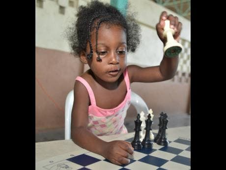 Three-year-old Tajarie Hayden from the Denham Town community makes a chess move.