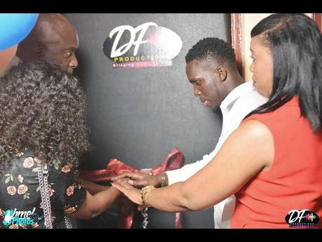 Dannareo Fearon (second right) is rather focused as he gets some help to cut the ribbons at the opening of his studio.