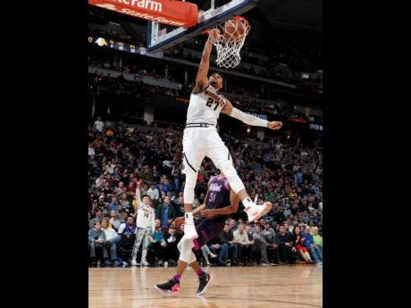 Denver Nuggets guard Jamal Murray dunks the ball for a basket as Minnesota Timberwolves forward Keita Bates-Diop looks on in the second half of their NBA basketball on Tuesday in Denver. The Nuggets won 133-107.