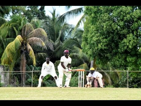 Manchester High School's batsman Oniel Roberts (centre) plays a shot in the semi-final of the ISSA/Grace Headley Cup at the STETHS Sports Complex on Wednesday.