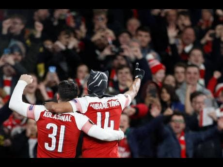 Arsenal's Pierre-Emerick Aubameyang (right) celebrates after scoring his side's third goal during the Europa League round-of-16, second-leg match between Arsenal and Rennes at the Emirates stadium in London, yesterday.