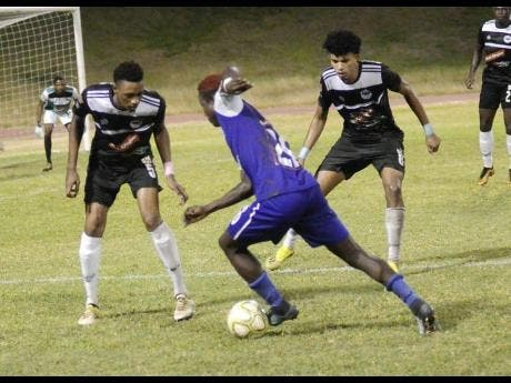 FC Reno's Fancy-Hue Stewart (centre) drives forward while being closely marked by Cavalier's Jamoy Topey (left) and his teammate Leonardo Rankine during their Red Stripe Premier League match at the Stadium East field earlier this season. FC Reno was relegated from the Red Stripe Premier League yesterday after going down 3-2 to Mount Pleasant FA.