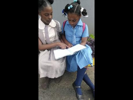 Gabrielle (left) helps Brittannia with her schoolwork.