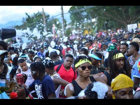 Revellers are doused with foam along Ring Road during the UWI Carnival Band March.