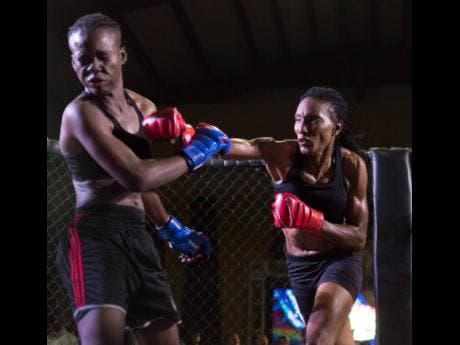 Shanice Blake (left) of Ruthless Sports Academy is left reeling after a hard right from Lisa Frazer, representing the Jamaica Defence Force (JDF) and Wushinkido Lion Pride Gym. The ladies competed for the female flyweight mixed martial arts championship at the Rough Fight League fight night held at the Douglas Orane Auditorium at Wolmer's Boys School on Saturday, March 9.