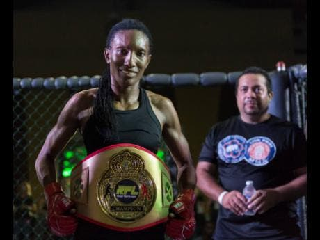 Frazer poses with her RFL Female Flyweight championship belt. Also pictured is Daniel Chacko-Wilmot (background), vice-president of Mixed Martial Arts Jamaica Sport.