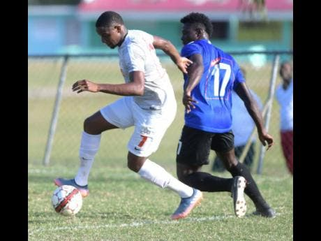 UWI's Ryan Miller (left) dribbles away from Cavalier player Kamoy Simpson in their Red Stripe Premier League encounter at the UWI Bowl on Sunday, March 11, 2018.