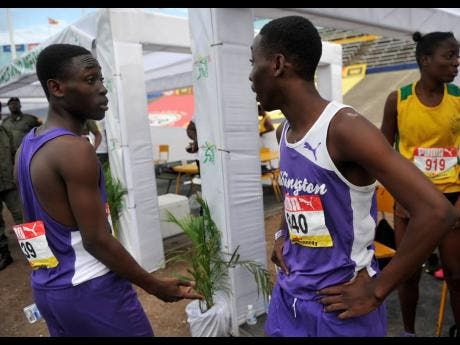 SHORN HECTOR  Giovouni Henry (left) of Kingston College talks with twin brother Gianni after competing in the Class Two boys 800m semi-finals on day three of the ISSA/GraceKennedy Boys and Girls' Athletics Championships.