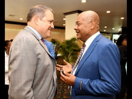 President of CONCACAF Victor Montagliani talks with Michael Ricketts, the president of the Jamaica Football Federation, at a ceremony to announce that Jamaica will be   host venue for this year's  Gold Cup at The Jamaica Pegasus hotel, yesterday.
