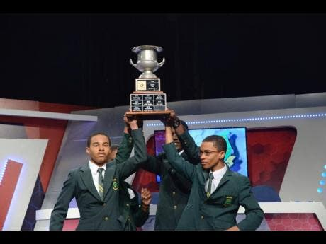 From left: St Jago High's Joel Henriques, Abigail Barnes (partially hidden), Leroy Casanova, and Chanarie Lindsay celebrate with the 2019 School's Challenge Quiz Trophy after defeating Kingston College in the final.