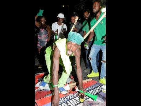A JLP supporter mimics a goat, as he and others jeered losing PNP candidate Damion Crawford's campaign promise. The supporters were gathered last night in Port Antonio to celebrate the victory of Ann-Marie Vaz in the Portland Eastern seat.