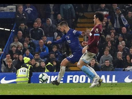 Chelsea's Eden Hazard scores his side's second goal during the English Premier League match between Chelsea and West Ham at Stamford Bridge stadium in London yesterday