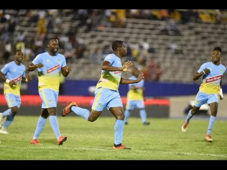 Keithy Simpson (centre) of Waterhouse FC celebrates a goal scored against Cavalier FC during the Red Stripe Premier League Semi-Final first-leg play-off at the National Stadium on Monday.