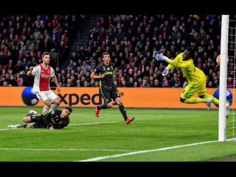 Ajax goalkeeper Andre Onana (right) fails to save the ball as Juventus' Cristiano Ronaldo (bottom left) scores his side's goal during their UEFA Champions League quarter-final first- leg match at the Johan Cruyff ArenA in Amsterdam, Netherlands, yesterday.