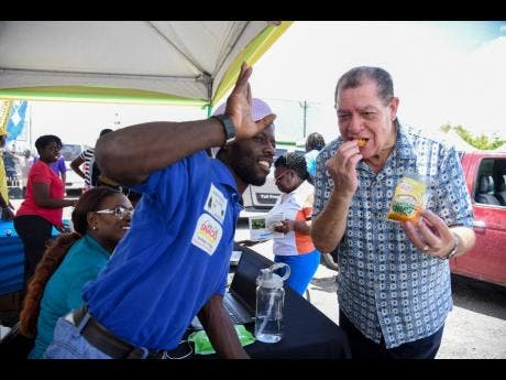 Agriculture Minister Audley Shaw (right) samples cocoa chips at the Clarendon Municipal Corporation-sponsored Clarendon Agro-Economic Symposium, held at St Gabriel's Church Hall in May Pen on Tuesday. At left is the chips maker, Gary Green.