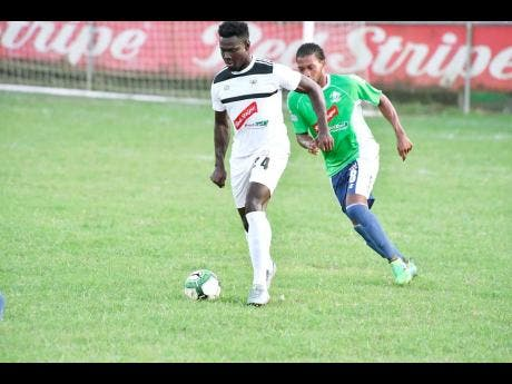 Kamoy Simpson (left) of Cavalier being tracked by Anthony Marks of Montego Bay United during their Red Stripe Premier League encounter at WesPow Park in Tucker, Montego Bay, on Thursday, December 28, 2017.