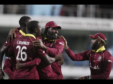 The Windies one-day international cricket team celebrates beating England by 26 runs in the second one-day international cricket match at the Kensington Oval in Bridgetown, Barbados, on Friday, February 22, 2019.