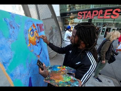 Artist Gift Davis works on a portrait of rapper Nipsey Hussle as fans wait in line to attend the public memorial at Staples Center in Los Angeles. (AP Photo/Ringo H.W. Chiu)