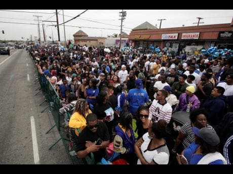 People gather outside The Marathon Clothing store to watch a funeral procession of rapper Nipsey Hussle.