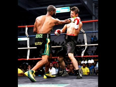 Sakima 'Mr Smooth' Mullings (left) lands a hard right on Alejandro Herrera during a boxing match at the National Indoor Sports Centre, in Kingston, on Wednesday, July 25, 2018.