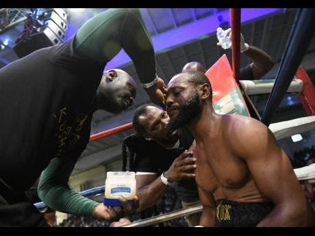 Sakima ' Mr Smooth' Mullings (right) receives instructions from coach Chris Brown (centre) at the end of a round during a boxing match against Alejandro Herrera at the National Indoor Sports Centre, in Kingston, on Wednesday, July 25, 2018.