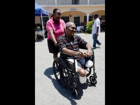 Alecia Salmon (left) assists wheelchair user Lancelot Harris at the Jamaica Health and Wellness Fair held at Lighthouse Assembly Church of God located in Spanish Town, St Catherine, last Friday.