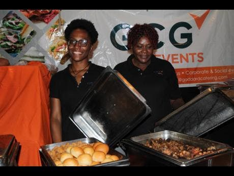 Kyria Simpson (left) and Paula Waysome of GCG Events give us a peek at what their VIP menu includes.