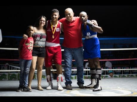 Local amateur boxer Arnold Anderson (right) poses with his Panamanian counterpart Alejandro Diaz (third left), Panamanian ambassador to Jamaica, Alexis Sandoval, and members of his family at the Jamaica Boxing Board's second Gloves For Guns event held at the Stanley Couch Gym in Kingston last Saturday.