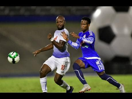 Javon East (left) of Portmore United is tackled by Mount Pleasant FA's Cardel Benbow in their second leg Red Stripe Premier League semi-final at the National Stadium in Kingston, yesterday.